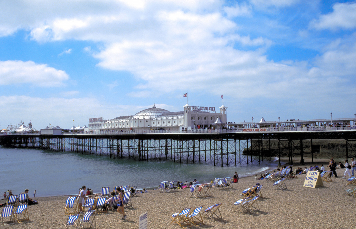 People on the beach by Brighton Pier, Brighton, East Sussex, England.