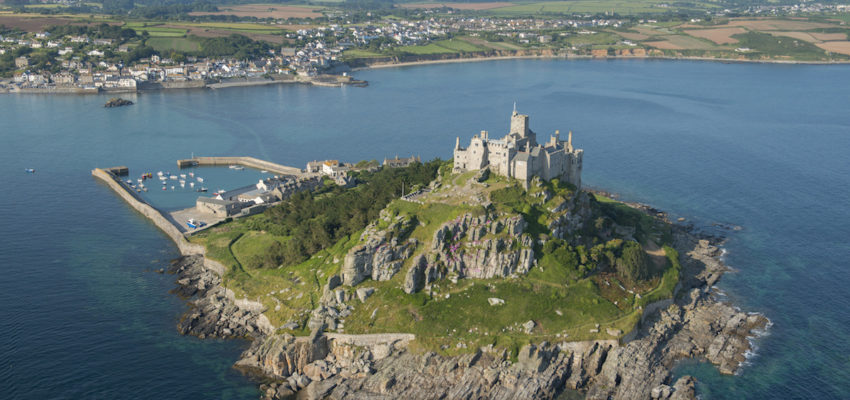 St Michaels Mount, a historic fortified building on a rocky outcrop in the Marazion bay, off the coast of Cornwall. Aerial view.