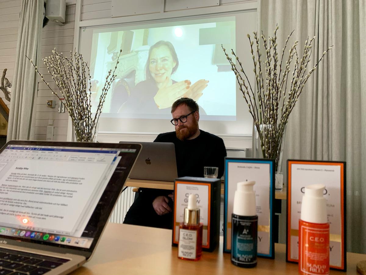 Sunday Riley syns på en skärm med moderatorn Craig framför sin dator