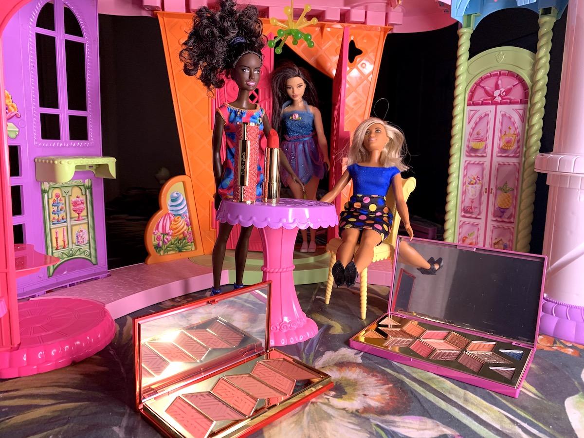 Rougepaletten och ögonskuggspaletten samt det röda läppstiftet från Barbie X Pur står i ett barbiehus med dockor.
