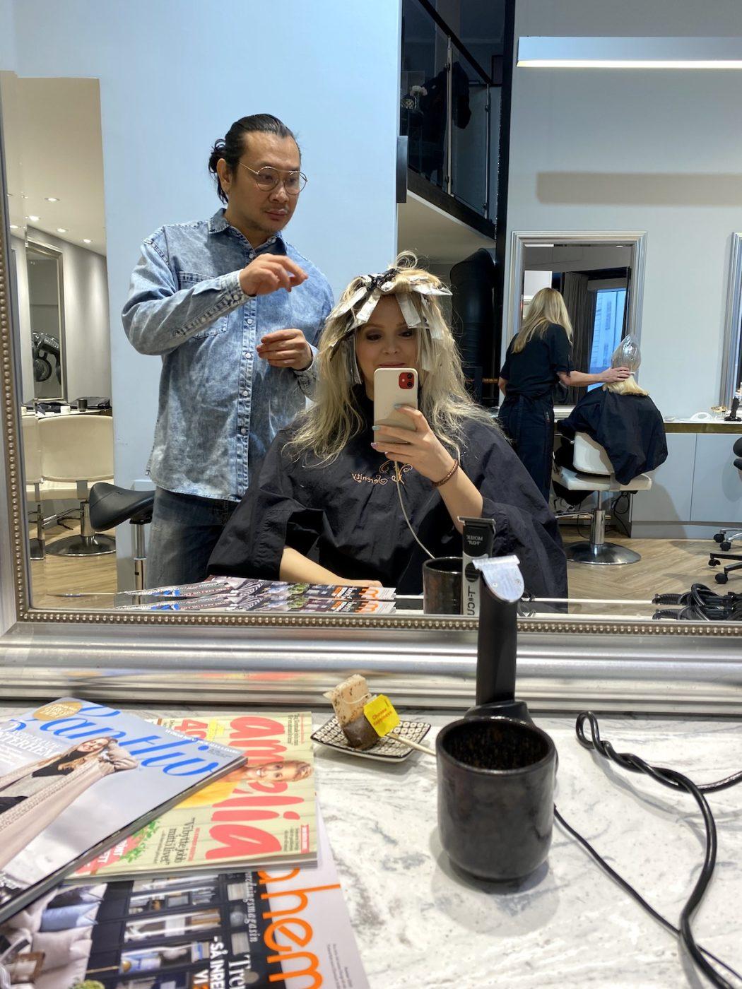 Daniel kollar om hårfärgen är färdig medan Elin sitter i frisörstolen