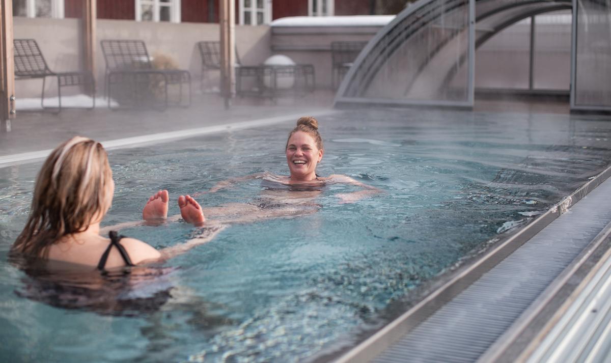 Elin och Johanna badar i poolen på Fågelbrohus. Johanna skrattar när Elin drar henne i fötterna.
