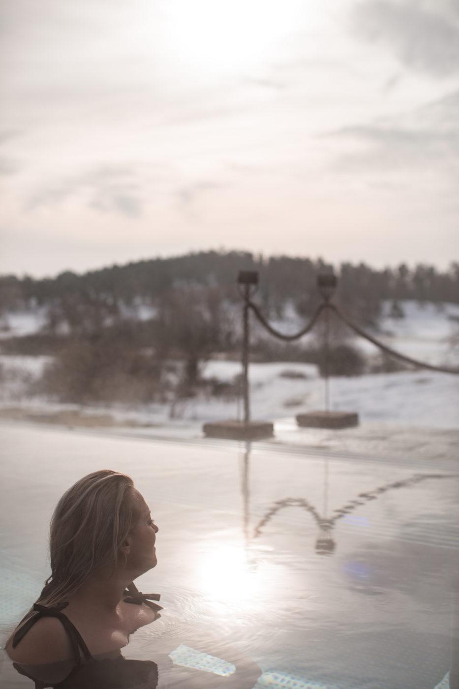 Elin njuter i den uppvärmda poolen.på Fågelbrohus. Hon har ansiktet mot solen.