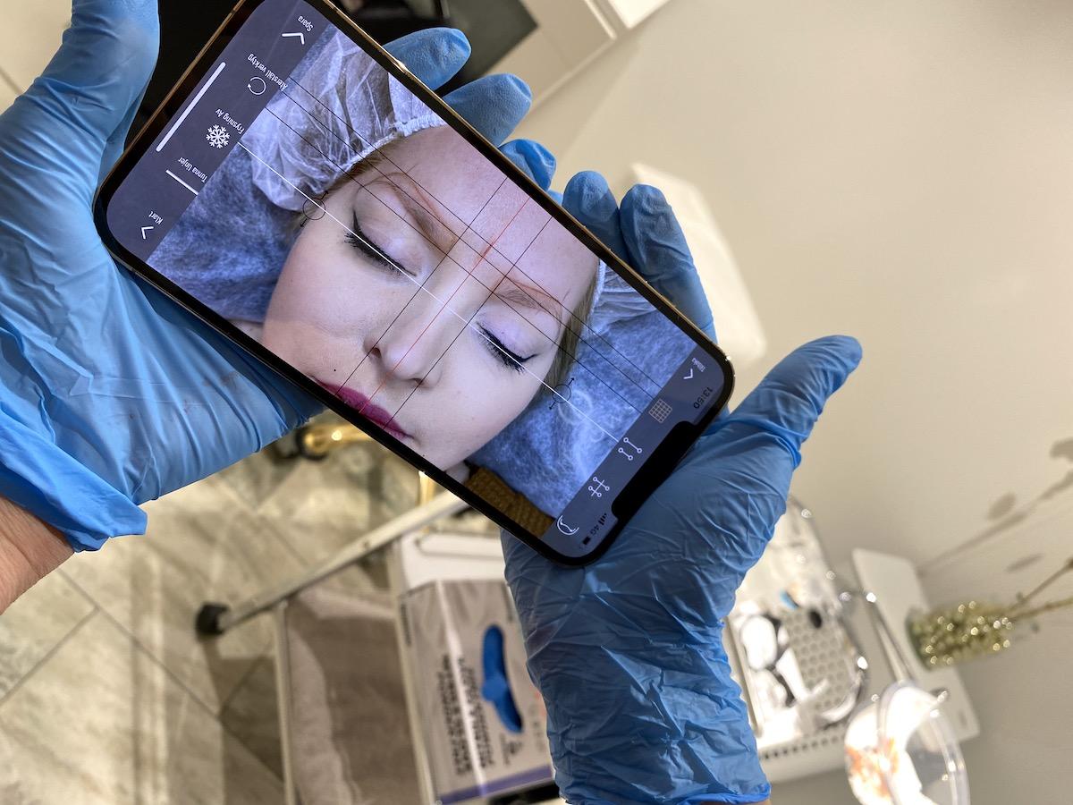 En mobil som hålls av två händer med blåa handskar. På mobilen syns en bild med Elins ansikte och flera streck.