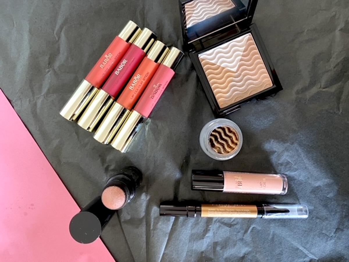 Alla samlade produkter från Babors vårkollektion. Bakgrunden är svart och rosa. På bilden syns flera sminkprodukter för läppar, ögon och hud.