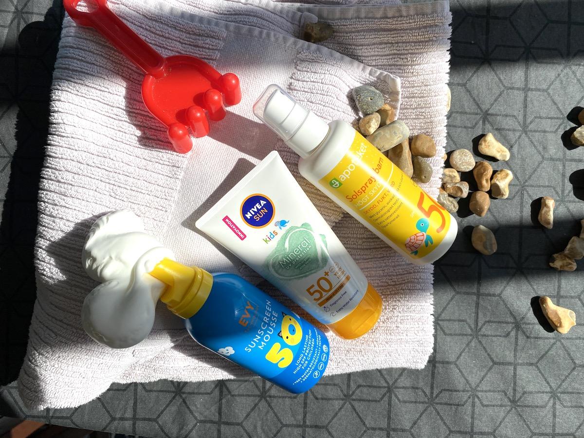 Solskydd till barn. Bild med tre produkter på en handduk. Det finns stenar utspridda och en sandleksak.