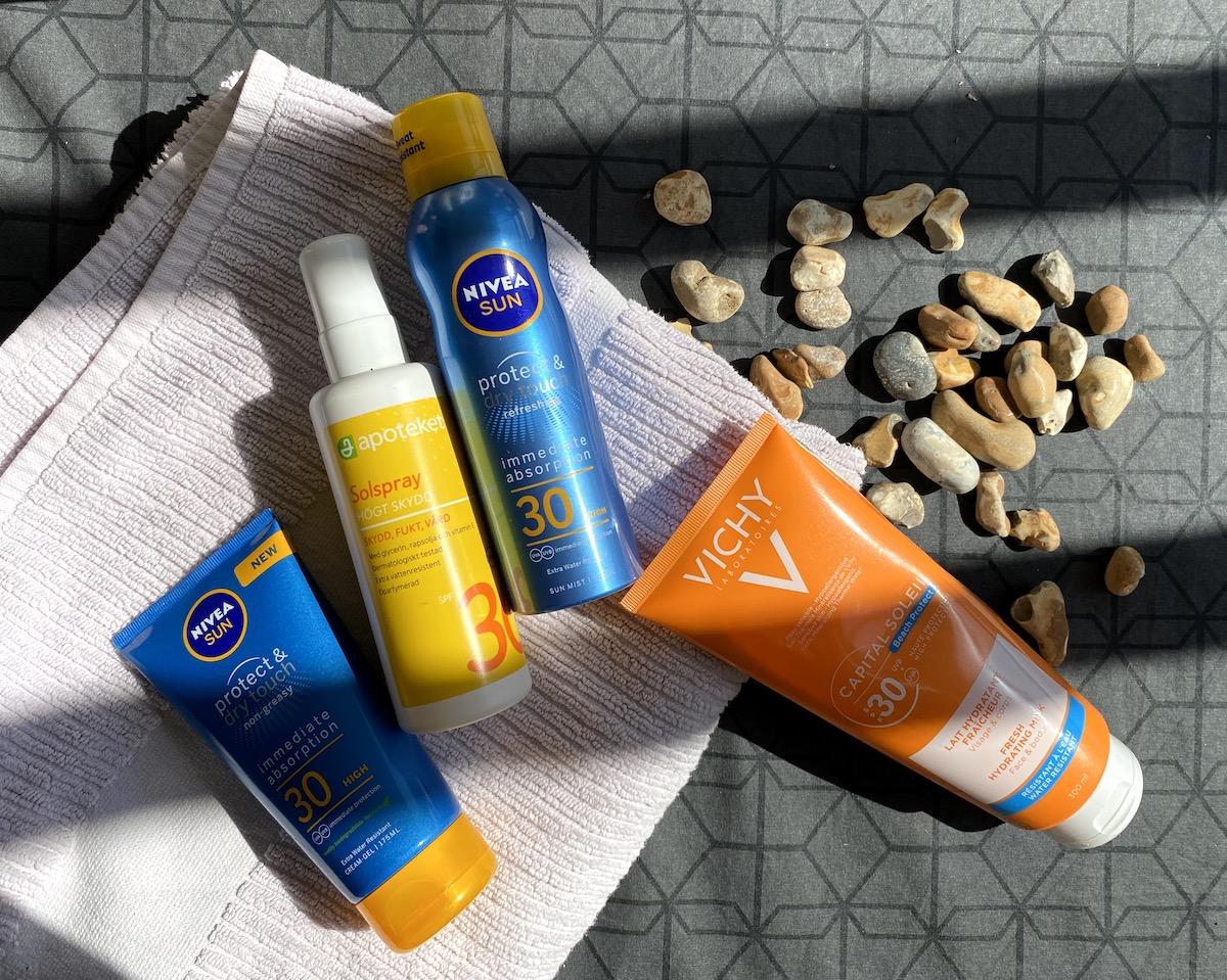 Fyra produkter i tub och flaska med bra solskydd för en snygg solbränna. Produkterna ligger på en vikt handduk och har små stenar bredvid sig. Handduken är rosa och underlaget grått.