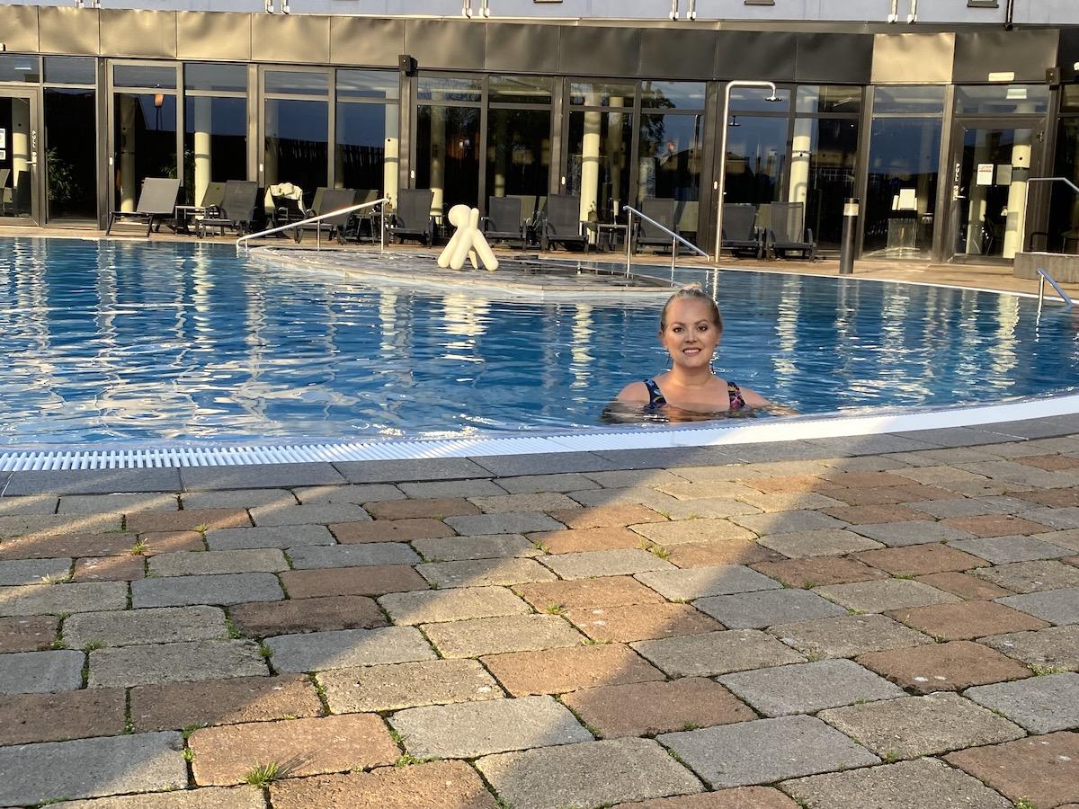 Elin ler och står i poolen. Håret är bakåtkammat