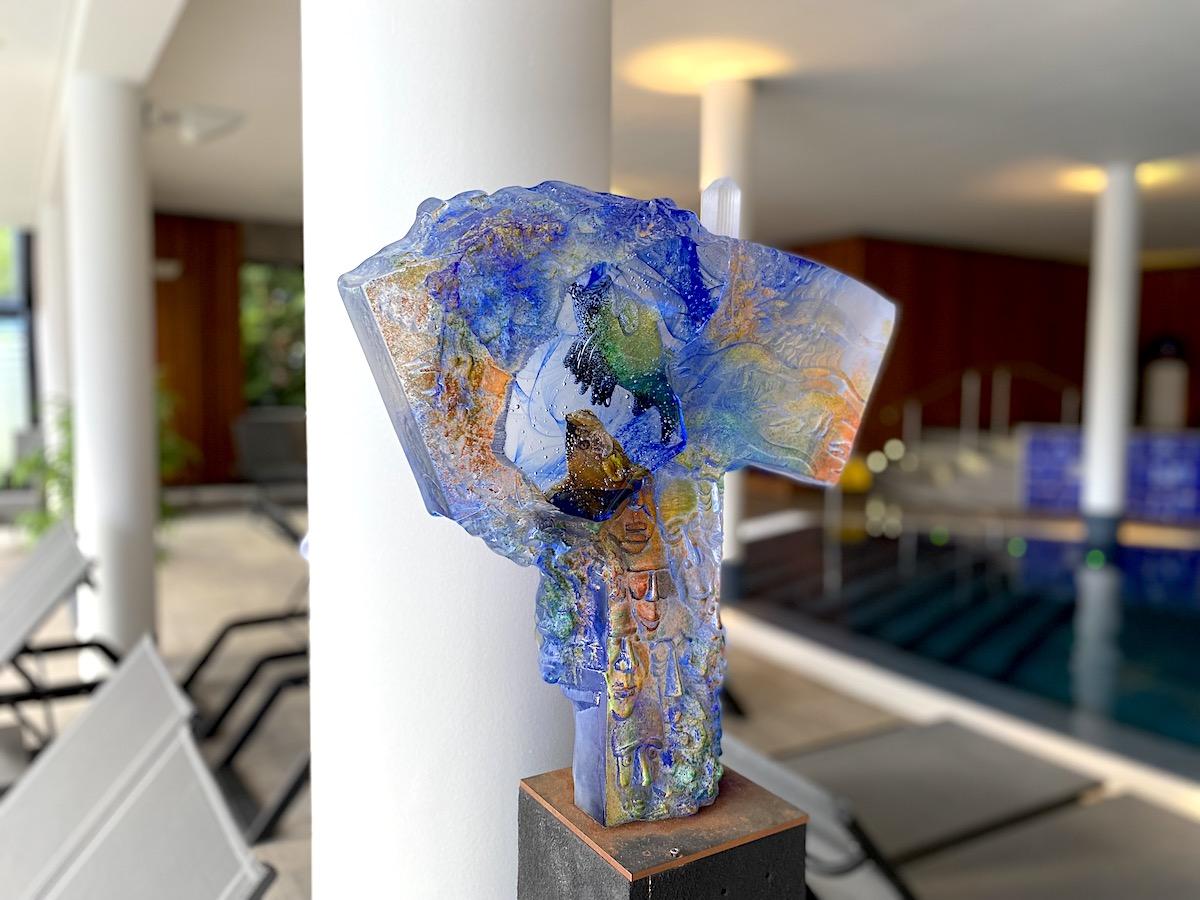En glasskulptur i blått och orange med poolen i bakgrunden