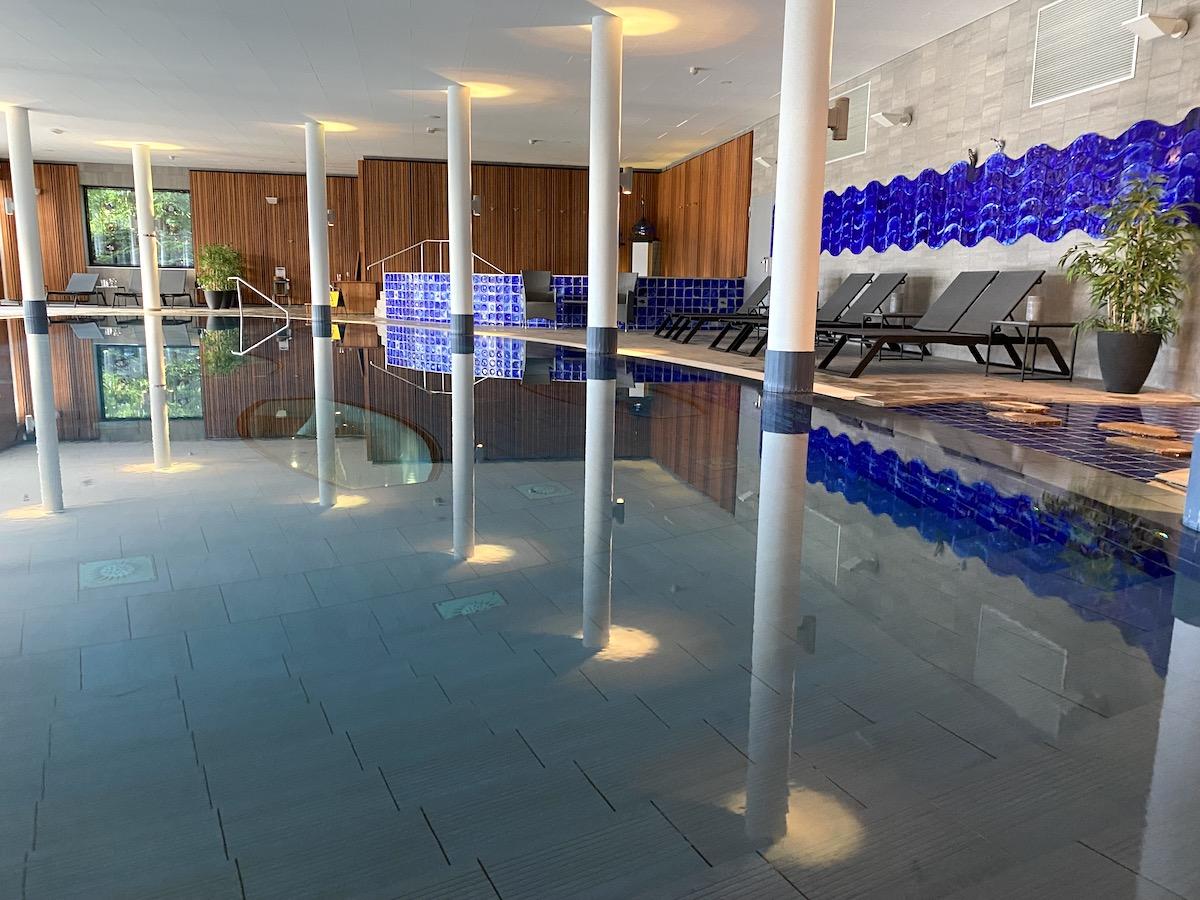 Den stora poolen på Kosta Boda Art Hotel med en mindre i bakgrunden. Färgerna går i blått ochbrunt och längs med en vägg står flera badstolar uppställda.