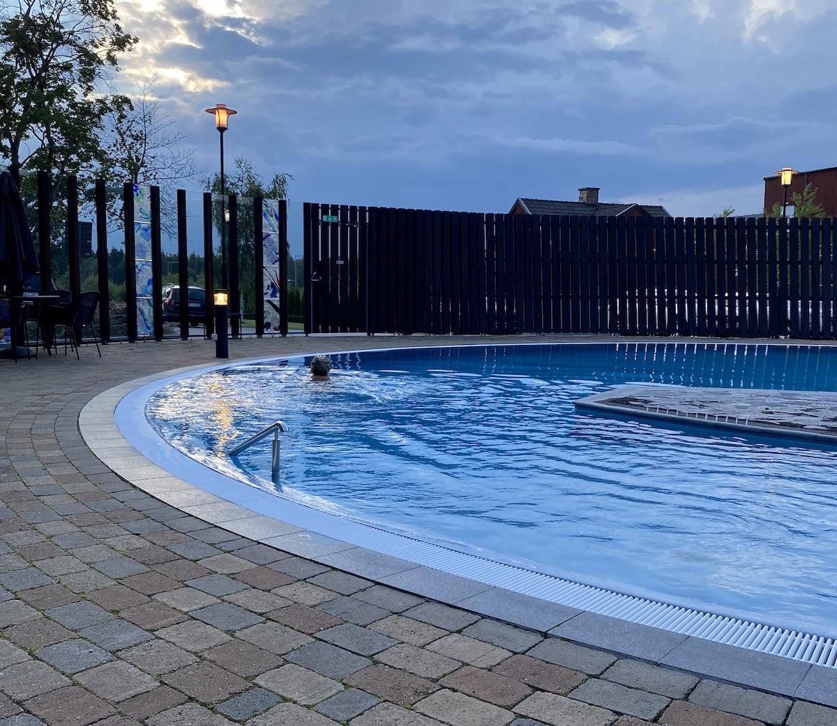 Det är nästan mörkt ute och Elin simmar i den rundade poolen.
