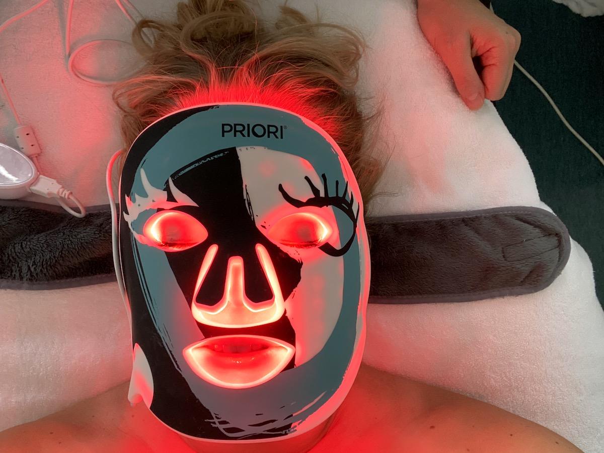 Elin har en mask som lyser på sig. Det står Priori på masken
