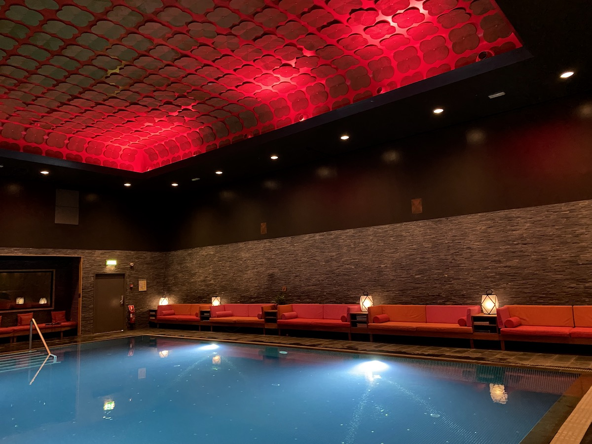 En pool med svarta väggar och röda lampor.