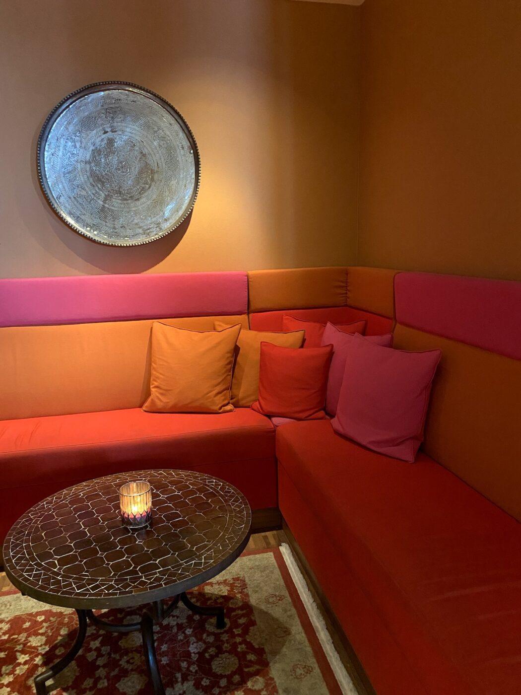 En soffa i rosa, orange och rött med ett marockanskt fat upphängt på väggen bakom.