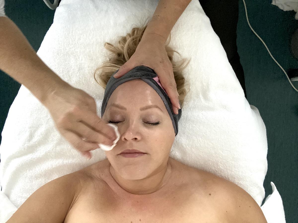 Elin ligger ner på en bänk med vita handdukar och får ansiktet tvättat
