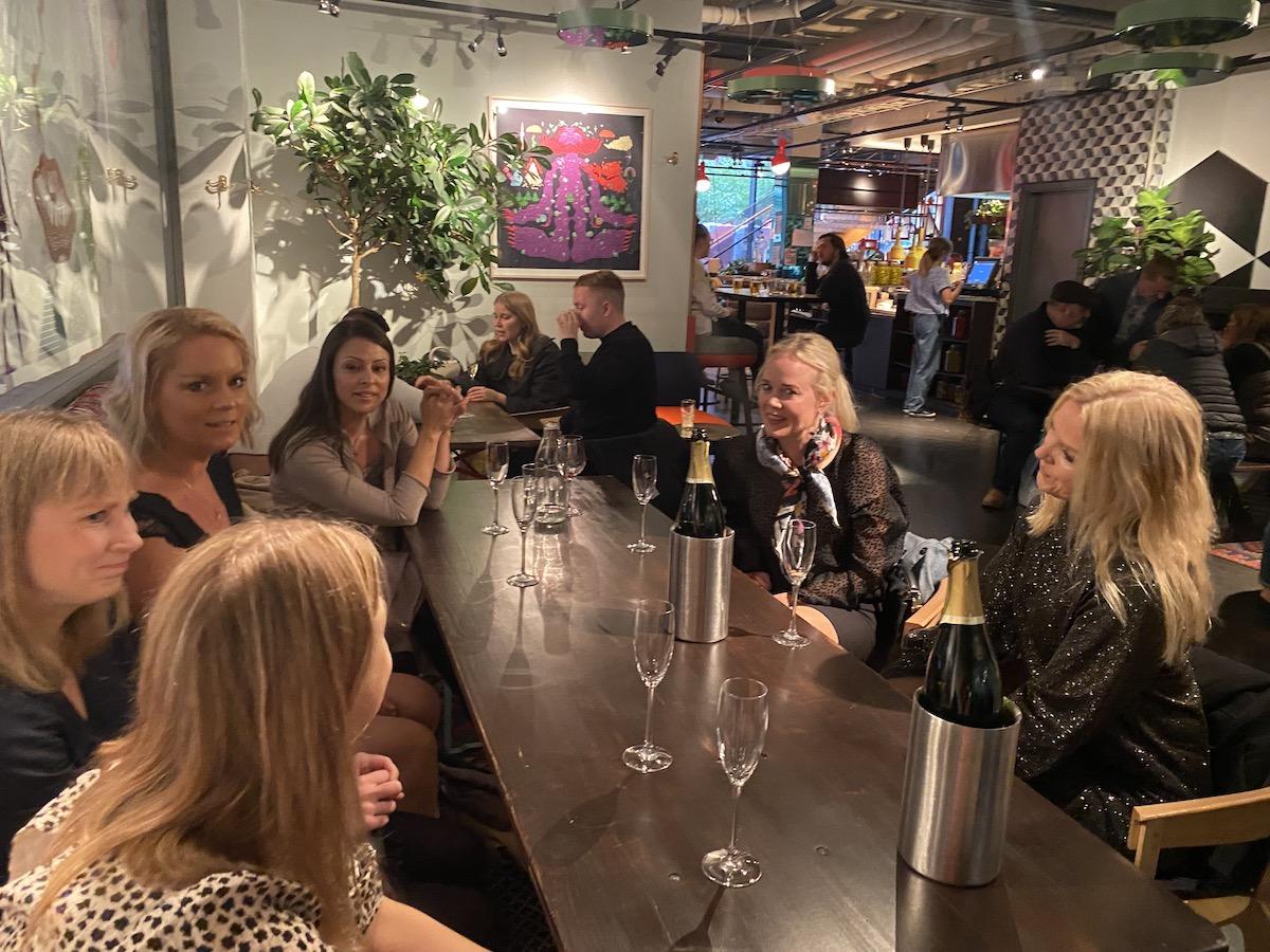 Flera kvinnor sitter runt ett bord. Det finns cava och vinflaskor på bordet. De är på Hobo