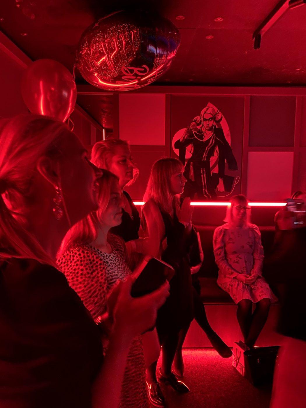 Flera kvinnor syns på bilden som har rött ljus. Alla tittar åt samma håll.
