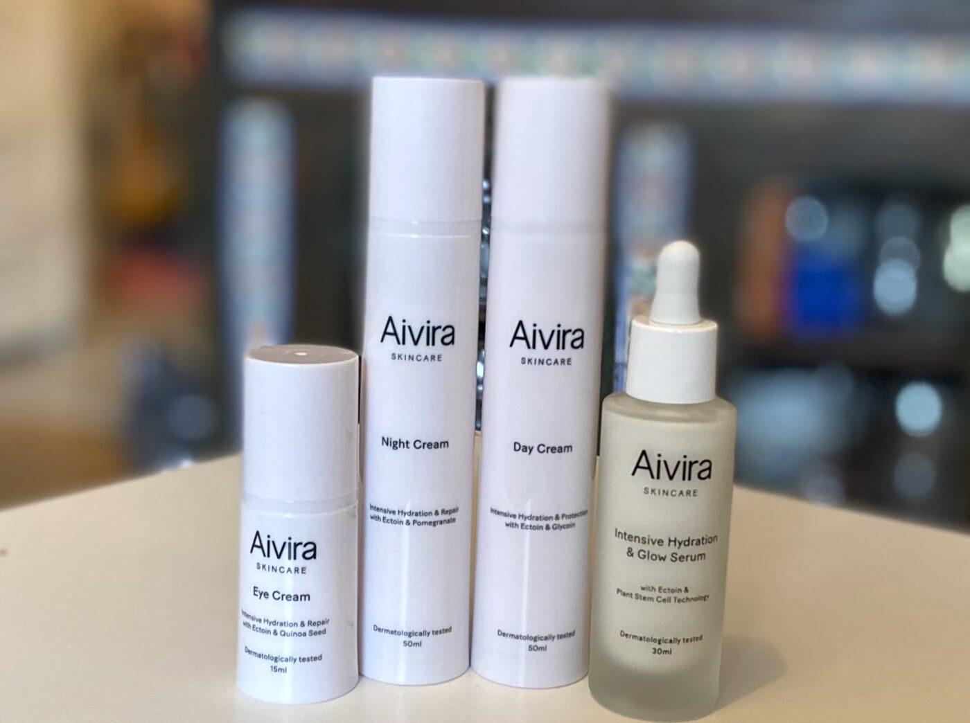Alla produkterna från Aivira står på rad. Det är tre flaskor i plast och en i glas med pipett. Alla är vita med svart text. Bakgrunden är blurrad.